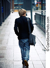 Teenage Boy - Teenage boy walking away from camera in...