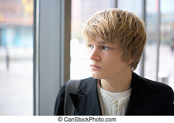 Teenage Boy - Teenage boy looking out window in urban...