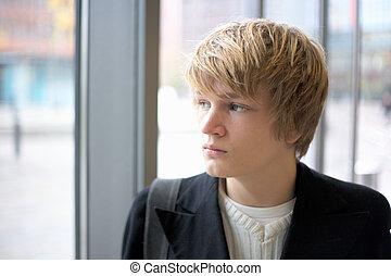Teenage Boy - Teenage boy looking out window in urban...