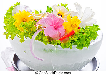 Green salad with tomatoes and various edible flowers in a...