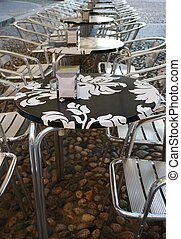 Outdoor cafe - Row of metal chairs and black and white...