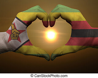 Gesture made by zimbabwe flag colored hands showing symbol...