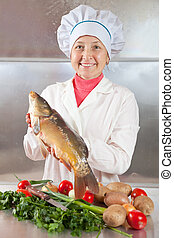 Cook woman with carp fish in kitchen