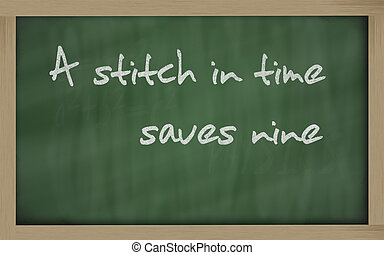 """ A stitch in time saves nine "" written on a blackboard -..."