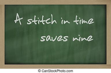 """ A stitch in time saves nine "" written on a blackboard -..."