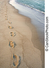 Foot imprints beside waves reaching margin. Romantic stroll.