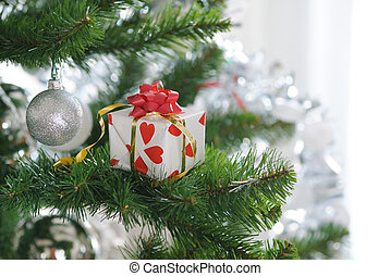 gift on christmas tree - gift with red bow on christmas tree...