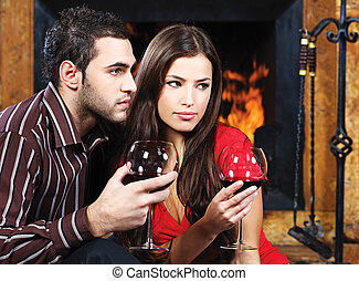 Romantic couple near fireplace drinking red wine