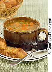 Hearty vegetable soup with artisan baguette in vertical...