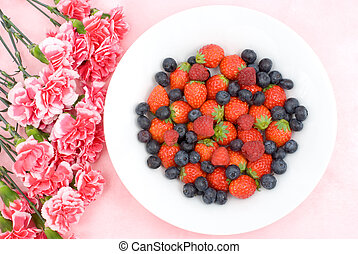 Three kinds of berry with carnation bouquet