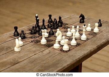 hand-made chessboard on wooden table, selective focus
