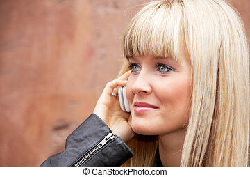 Young Woman - Young woman using mobile phone by building...