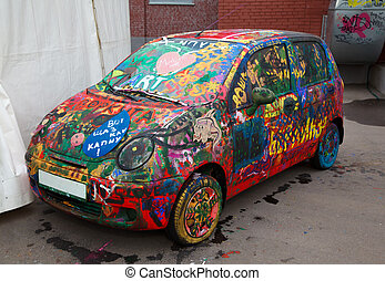 Old car painted by multi-coloured drawings.