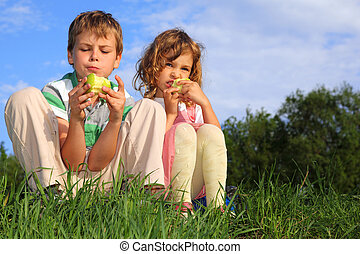 Two lovely children sit on a grass, against the blue sky and...