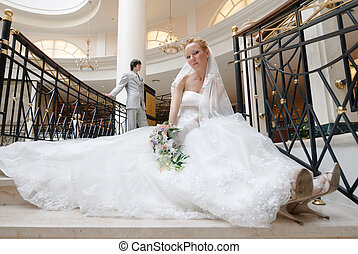 Bride in beautiful wedding dress sits on wide spiral...