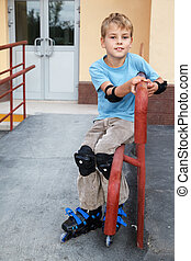 Boy in rollerblades, knee and elbow pads, sitting on the...