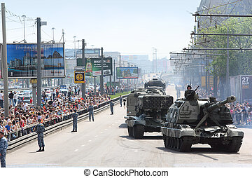 MOSCOW - MAY 9: People looks on weaponry and tank on road on...