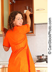beautiful young woman standing in kitchen and opens ?upboard