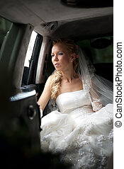 Bride in wedding dress sits in limousine and looks out in...