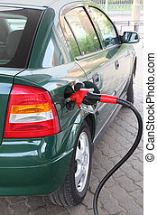 red pump for refueling filling green car on station, summer...
