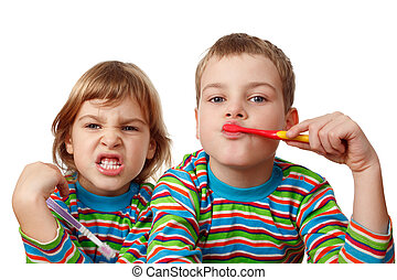 Brother and sister in same shirts brush their teeth on white...
