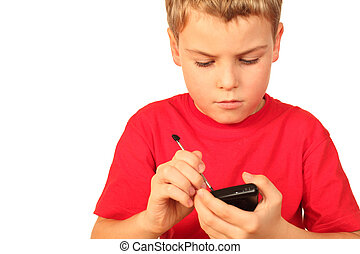 smart small boy in red sports shirt writes note in telephone...