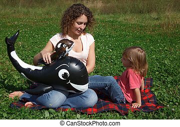 Mom and daughter play on grass on sunny day with inflatable...