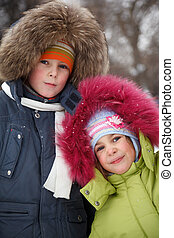 Brother and sister smiling looking into camera in winter forest, in jackets with fur hoods on their heads.