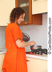 beautiful young woman standing in the kitchen and prepare food