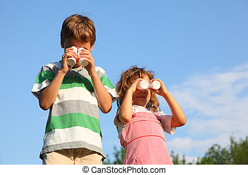 The girl and the boy, against the blue sky play with small bottles from yoghurt, representing the binocular.