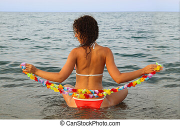 beautiful young woman dressed in bathing suit holding garland of hawaiian flower and seats in the water on sea