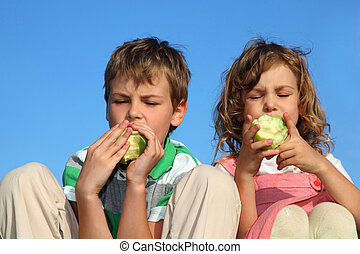 Two beautiful children, against the blue sky eat the big green apples.