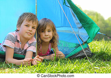 Little brother and sister lying inside blue tent on green...