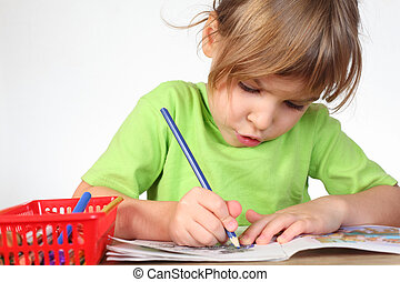 little girl in green shirt painting in notebook, blue pencil in hand, half body, isolated