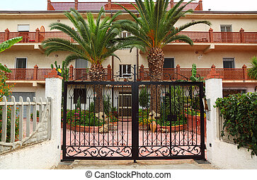 Forged black gate of sanatorium. palm trees and buildings of...