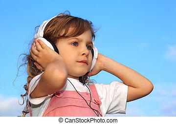 The lovely little girl, against the blue sky, listens to music through ear-phones.