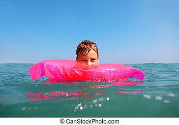 The little boy floating in sea on inflatable pink matrese. shot from underwater box, water on box blurry
