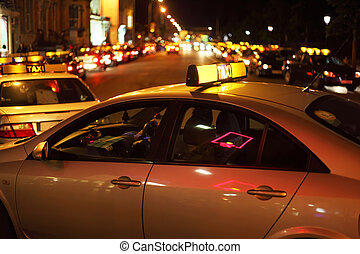 city nightlife. few taxis wraps on road. Many bright lights