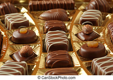 many chocolate appetizing candys with icing in golden box