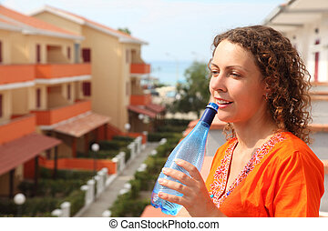 beautiful young woman standing on balcony and holding bottle and drink from it clean water. in background, sea, beach