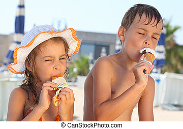 Brother and little sister eating ice cream after bathing. Girl wearing swimsuit and hat