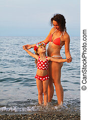 young mother and little daughter standing on beach.  on head of girl is garland of Hawaiian flowers
