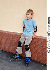 Boy in rollerblades, knee and elbow pads standing near wall.
