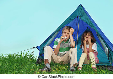 Small children have a rest on the nature, sit near tent and eat sweets.