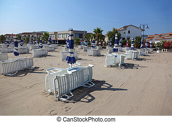many white striped deck chairs and beach umbrellas are on...