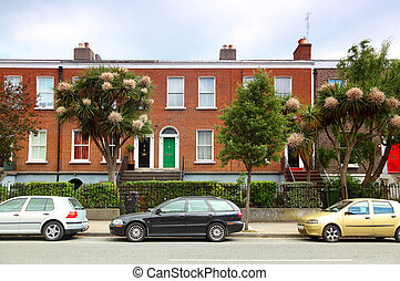 cars parked near two-story red brick house on street in...