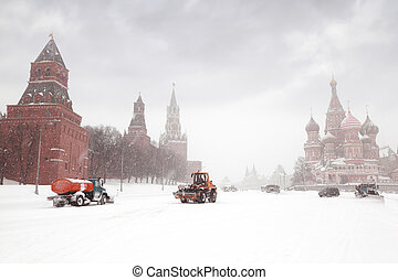 Snow-remover trucks and tractor near Red Square, St Basil Temple and Spasskaya Tower of Kremlin in Moscow, Russia at wintertime during snowfall