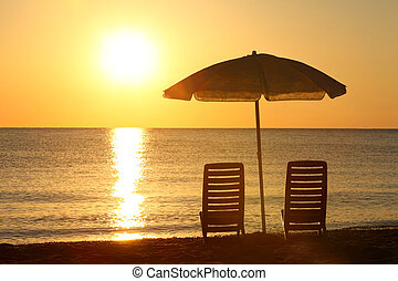 Two empty chairs stand on beach under opened umbrella with...