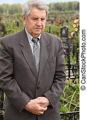 old sad senior in grey suit standing on cemetery and looking...
