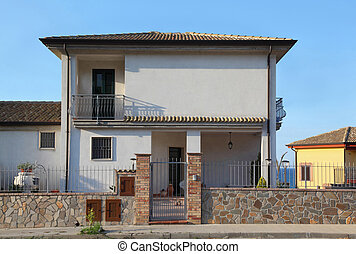 White two-storeyed cottage behind fence with court and...